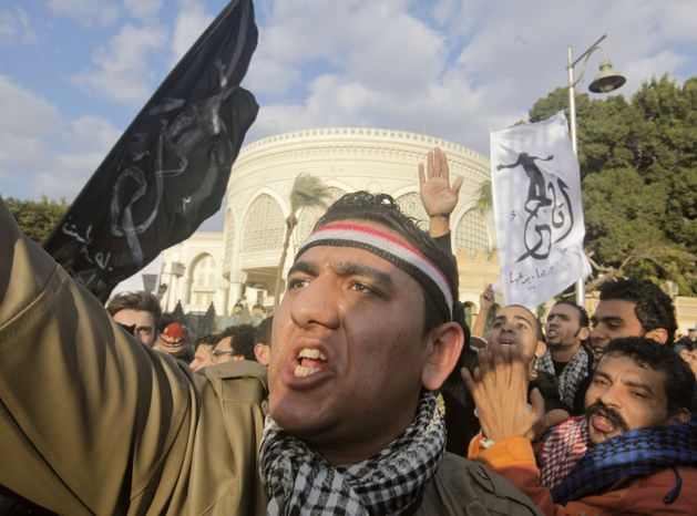 """Egyptians shout slogans during a demonstration against President Mohammed Morsi in front of the presidential palace in Cairo on Feb. 1, 2013. Arabic on the banner at right reads, """"I'm free.'"""" (Associated Press)"""