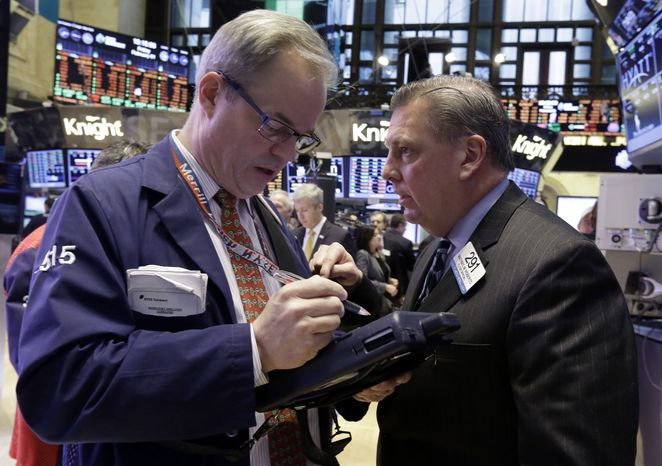 Traders David O'Day (left) and Mathias Roberts work on the floor of the New York Stock Exchange on Feb. 1, 2013. (Associated Press)