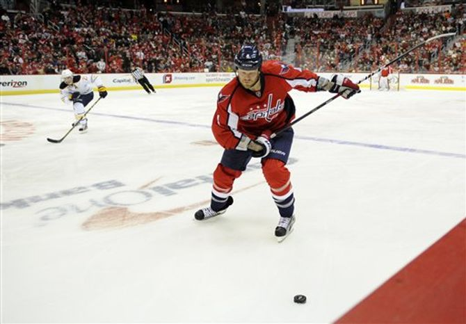 Washington Capitals defenseman John Erskine (4) chases the puck against the Buffalo Sabres during the second period of an NHL hockey game, Sunday, Jan. 27, 2013, in Washington. (AP Photo/Nick Wass)