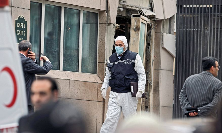 Emergency personnel are seen in front of a side entrance to the U.S. Embassy in Ankara, Turkey, after a suicide bomber detonated an explosive device there Friday. The blast also killed a Turkish security guard. (Associated Press)