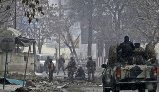 ** FILE ** Security men with the Afghan intelligence services inspect the scene following a militant attack in Kabul, Afghanistan, on Wednesday, Jan. 16, 2013. Six militants wearing suicide vests, including one driving a car packed with explosives, attacked the gate of the Afghan intelligence, setting off a blast that reportedly caused several deaths and wounded at least 30 civilians, officials said. (AP Photo/Musadeq Sadeq)