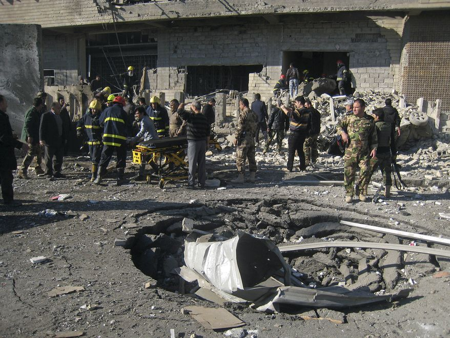 Iraqi civilians and security forces inspect a crater caused by a car bomb attack in Kirkuk, Iraq, 180 miles north of Baghdad, on Sunday, Feb. 3, 2013. (AP Photo/Emad Matti)