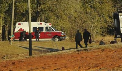 Police and emergency personnel remain on site at the property of Jimmy Lee Sykes, a suspect accused of holding a 5-year-old boy hostage in an underground bunker, on Saturday, Feb. 2, 2013, in Midland City, Ala. (AP Photo/al.com, Joe Songer)
