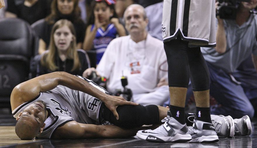 San Antonio Spurs' Tim Duncan lies on the floor after being injured on a play during the first half against the Washington Wizards during an NBA basketball game Saturday, Feb. 2, 2013, in San Antonio. The Spurs said via Twitter that Duncan sprained his right ankle and left knee and would not return to the game. (AP Photo/San Antonio Express-News, Edward A. Ornelas)