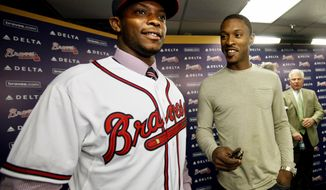 Justin Upton, left, acquired by the Atlanta Braves from the Arizona Diamondbacks in a seven-player deal last week, stands with his brother B.J, Upton, right, who signed a five-year, $75.25 million contract with Atlanta in November, at Justin's first Atlanta news conference, Tuesday, Jan. 29, 2013, in Atlanta. (AP Photo/David Goldman)
