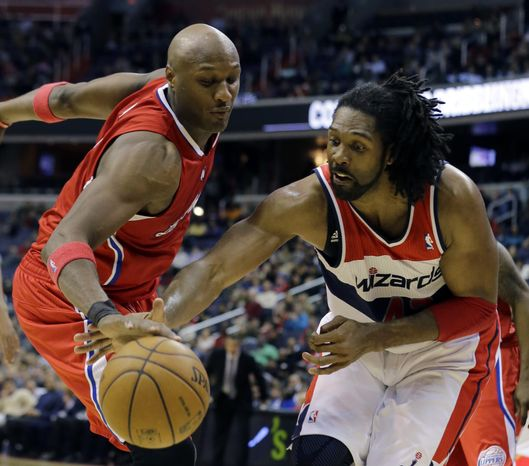 Los Angeles Clippers forward Lamar Odom (7) and Washington Wizards center Nene go for the loose ball in the second half of the Wizards' 98-90 win on Feb. 4, 2013, in Washington. (Associated Press)