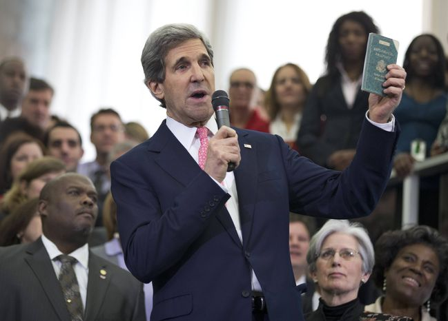 New Secretary of State John Kerry shows his first diplomatic passport he got when he was 11 years old when his father was in the foreign service, during a ceremony welcoming him as the 68th secretary of state, Monday, Feb. 4, 2013, at the State Department in Washington. (AP Photo/Manuel Balce Ceneta)