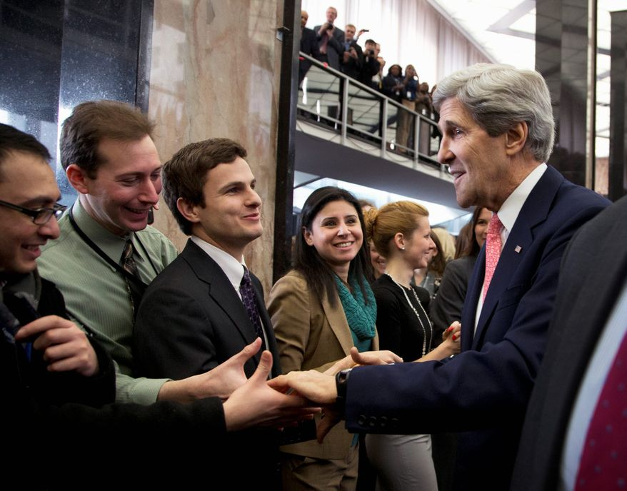 New Secretary of State John F. Kerry is greeted by State Department staff as he arrives during a ceremony welcoming him as the 68th secretary of state on Monday. He succeeds Hillary Rodham Clinton in the Cabinet post. (Associated Press)