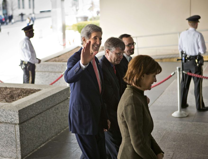Secretary of State John Kerry, escorted by staff, waves as he begins his first week on the job, as he arrives at the State Department in Washington, Monday, Feb. 4, 2013. The former chairman of the Senate Foreign Relations Committee and presidential candidate, replaces Hillary Rodham Clinton as the top U.S. diplomat. (AP Photo/J. Scott Applewhite)