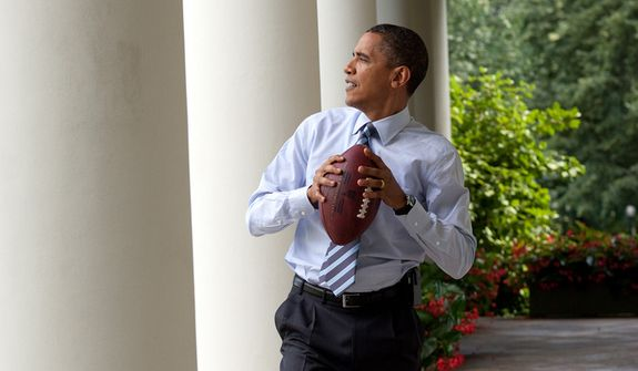 President Obama gets ready to toss a football in this photo posted on his Twitter feed moments before the Super Bowl kickoff between the Ravens and 49ers. It was taken in 2010. ** FILE **