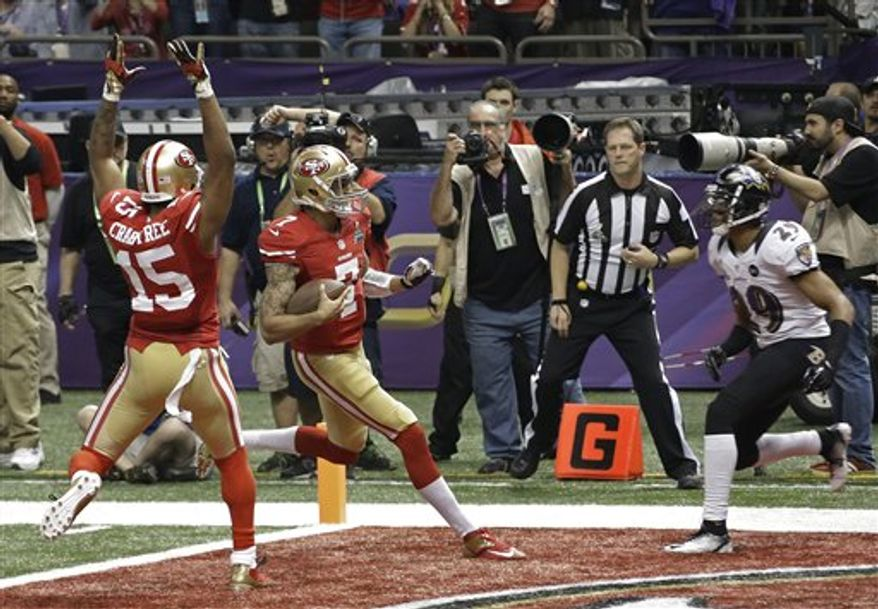 San Francisco 49ers quarterback Colin Kaepernick (7) runs into the end zone for a 15-yard touchdown run as Baltimore Ravens cornerback Cary Williams (29) and 49ers wide receiver Michael Crabtree (15) watch during the second half of the NFL Super Bowl XLVII football game Sunday, Feb. 3, 2013, in New Orleans. (AP Photo/Gene Puskar)