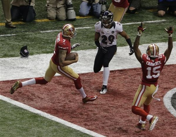San Francisco 49ers quarterback Colin Kaepernick (7) runs the ball in for a 15-year touchdown against the Baltimore Ravens during the second half of the NFL Super Bowl XLVII football game Sunday, Feb. 3, 2013, in New Orleans. Ravens' Cary Williams (29) looks on as 49ers wide receiver Michael Crabtree (15) celebrates. (AP Photo/Charlie Riedel)