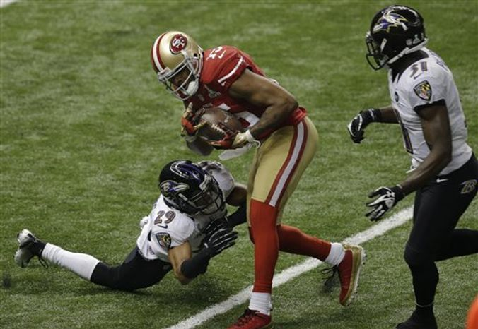 San Francisco 49ers wide receiver Michael Crabtree (15) makes a catch for a 31-yard touchdown as Baltimore Ravens cornerback Cary Williams (29) and safety Bernard Pollard (31) defend during the second half of the NFL Super Bowl XLVII football game Sunday, Feb. 3, 2013, in New Orleans. (AP Photo/Gerald Herbert)