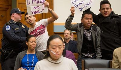 ANDREW HARNIK/THE WASHINGTON TIMES Members of United We Dream in the audience rose and held signs as Rep. Darrel E. Issa, California Republican, was being introduced to speak at an immigration hearing on Tuesday.
