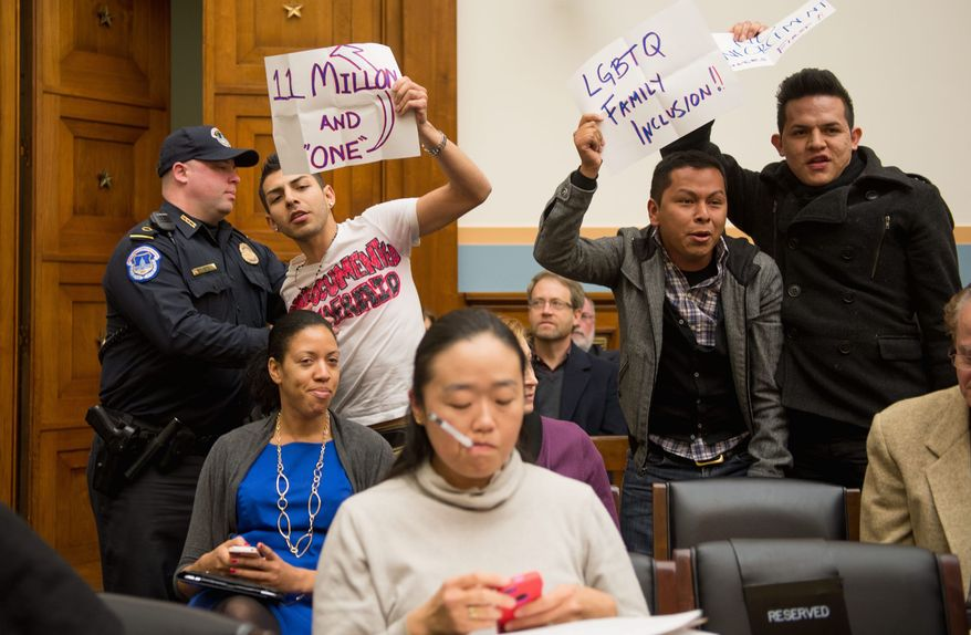 Members of United We Dream in the audience rose and held signs as Rep. Darrel E. Issa, California Republican, was being introduced to speak at an immigration hearing on Tuesday. (Andrew Harnik/The Washington Times)