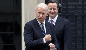U.S. Vice President Joseph R. Biden, left, gestures at photographers as British Prime Minister David Cameron, behind, bids him farewell after their meeting at 10 Downing St. in London, Tuesday, Feb. 5, 2013. Biden met with Cameron on Tuesday and attended a meeting of the U.K. National Security Council on the final leg of his European trip. (AP Photo/Matt Dunham)