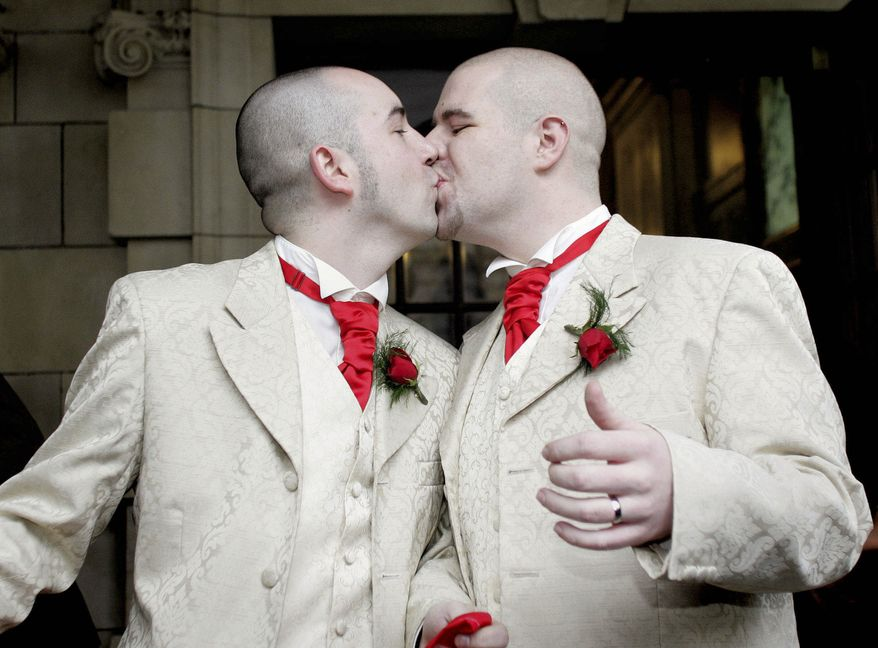 **FILE** Henry Edmont Cane (left) and partner Christopher Patrick Flanaghan kiss outside City Hall in Belfast, Northern Ireland, on Dec. 19, 2005. The two became the first male couple to win legal recognition for their partnership under a new British civil partnership law. (Associated Press)
