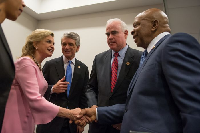 From left: Reps. Carolyn Maloney, New York Democrat, Scott Rigell, Virginia Republican, Patrick Meehan, Pennsylvania Republican, and Elijah Cummings, Maryland Democrat, great each other before a press conference Feb. 5, 2013, in Washington to introduce the first bipartisan bill in the House of Representatives during the 113th Congress, which would make firearms trafficking a federal crime and impose stronger penalties for straw purchasers who buy guns for convicted felons and others who are prohibited from buying guns on their own. (Andrew Harnik/The Washington Times)