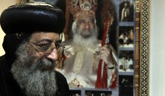 ** FILE ** In this Sunday, Nov. 4, 2012, file photo, Bishop Tawadros, 60, soon to be Pope Tawadros II greets well-wishers, not shown, after being named the 118th Coptic Pope in the Wadi Natrun Monastery complex northwest of Cairo, Egypt. Egypt's Coptic Christian pope has sharply criticized the country's Islamist leadership in an interview with The Associated Press, Tuesday, Feb. 5, 2013, saying the new constitution is discriminatory and that Christians should not be treated as a minority. (AP Photo/Roger Anis, El Shorouk Newspaper, File)