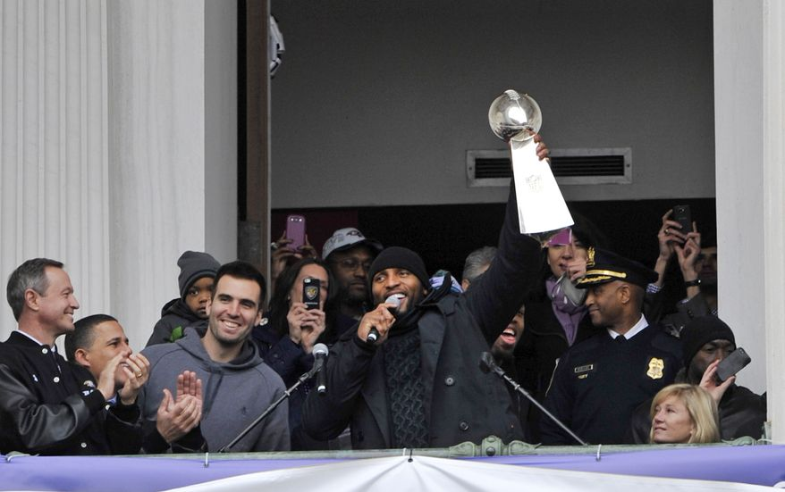 Baltimore Ravens linebacker Ray Lewis, holding the Vince Lombardi trophy, speaks to fans at a celebration at City Hall at the start of a Super Bowl victory parade Tuesday, Feb. 5, 2013, in Baltimore. Super Bowl MVP and Ravens quarteback Joe Flacco, third from left, smiles. The Ravens defeated the San Francisco 49ers in NFL football's Super Bowl XLVII 34-31 on Sunday. (AP Photo/Gail Burton)