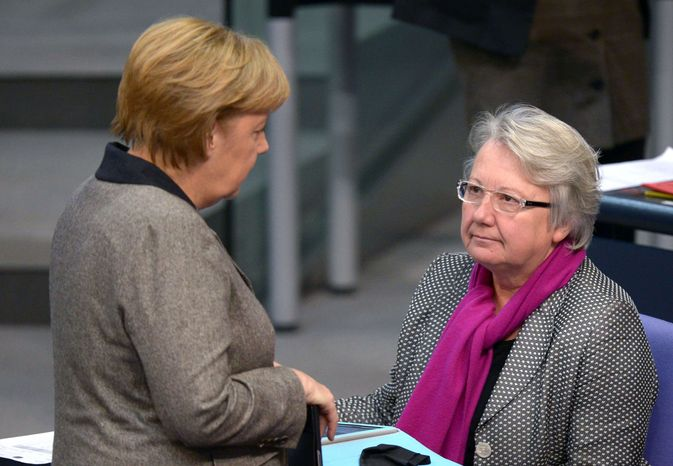 ** FILE ** in this Dec. 13, 2012, file photo German Chancellor Angela Merkel, left, talks to Education Minister Annette Schavan during a session of the German parliament Bundestag in Berlin, Germany. Schavan says she will not resign after a university stripped her of her doctorate because of plagiarism, and she vowed to fight the ruling. (AP Photo/dpa, Rainer Jensen, File)