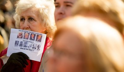 Mary Murphy of Bivalve, Md., holds a sign over her face as she listens to speaker at a pro-gun rights rally against a proposal by Maryland Governor Martin O'Malley that would ban assault weapons and require residents to obtain a license before purchasing handguns at Lawyers Park in front of the Maryland State House, Annapolis, Md., Wednesday, February 6, 2013. (Andrew Harnik/The Washington Times)