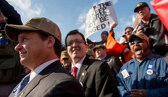 Dels. Steve Hershey (R-District 36), left, and Justin Ready (R-District 5A), second from left, and Issac Colbert of Annapolis, Md., bottom right, join others at a pro-gun rights rally against a proposal by Maryland Governor Martin O'Malley that would ban assault weapons and require residents to obtain a license before purchasing handguns at Lawyers Park in front of the Maryland State House, Annapolis, Md., Wednesday, February 6, 2013. (Andrew Harnik/The Washington Times)