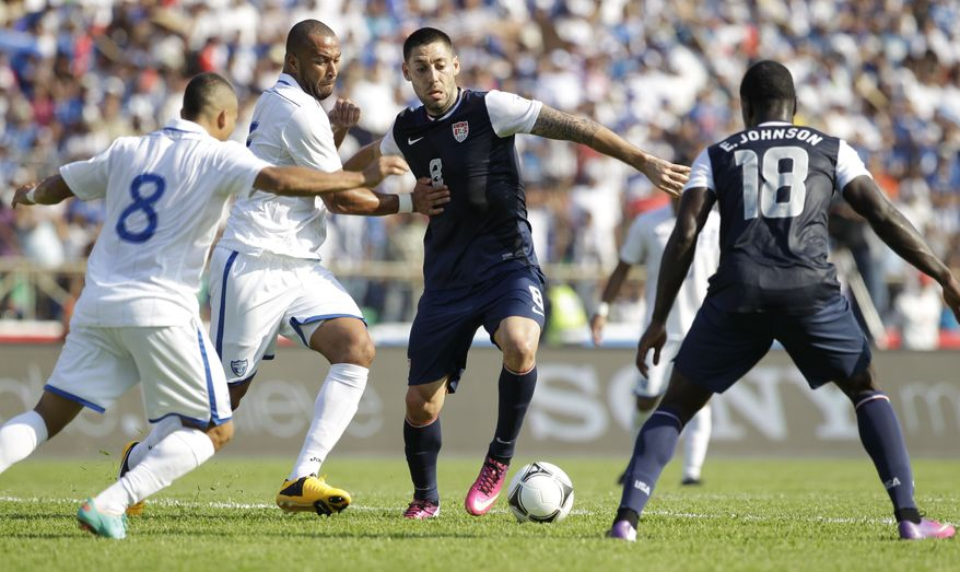 U.S. Clint Dempsey, second from right, is challenged by Honduras' Victor Bernardez, second from left, during a 2014 World Cup qualifying soccer game in San Pedro Sula, Honduras, Wednesday Feb. 6, 2013. (AP Photo/Moises Castillo)