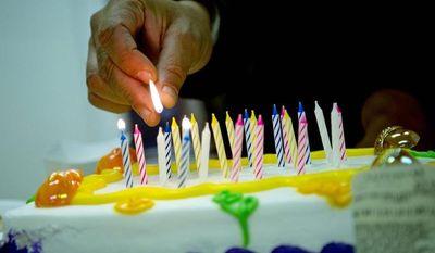Michelangelo Payne lights the candles on a birthday cake for volunteer Filomena Machado at Mount Gilead Baptist Church. (The Washington Times)