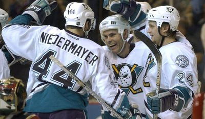 **FILE** Anaheim Mighty Ducks' Adam Oates, center, gets a hug from teammates Rob Niedermayer, (44) and Ruslan Salei, (24), after his second period goal against the Minnesota Wild during Game 4 of the NHL Western Conference finals in Anaheim, Calif., Friday, May 16, 2003. (AP Photo/Kevork Djansezian)