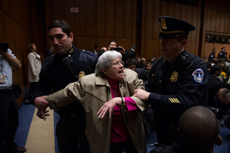 An anti-war protester is removed as John O. Brennan testifies before the Senate Select Committee on Intelligence at a hearing on Capitol Hill in Washington on Thursday, Feb. 7, 2013, on his nomination to head the Central Intelligence Agency. (Andrew Harnik/The Washington Times)