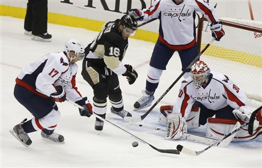 Pittsburgh Penguins' Brandon Sutter (16) tries to shoot the puck as Washington Capitals goalie Michal Neuvirth (30) and Capitals' Wojtek Wolski (17) defend in the first period of an NHL hockey game Thursday, Feb. 7, 2013, in Pittsburgh. (AP Photo/Keith Srakocic)