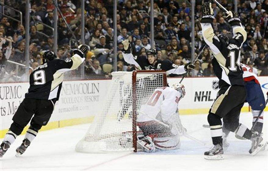 Pittsburgh Penguins' Pascal Dupuis (9) celebrates his goal against Washington Capitals goalie Michal Neuvirth (30) with Sidney Crosby, center, and Chris Kunitz (14) in the second period of the NHL hockey game Thursday, Feb. 7, 2013, in Pittsburgh. (AP Photo/Keith Srakocic)