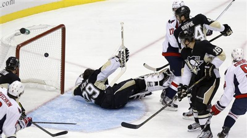 Pittsburgh Penguins goalie Marc-Andre Fleury (29) loses his mask as the puck goes over him for a goal by Washington Capitals' Mike Ribeiro, right, in the first period of the NHL hockey game Thursday, Feb. 7, 2013, in Pittsburgh. (AP Photo/Keith Srakocic)