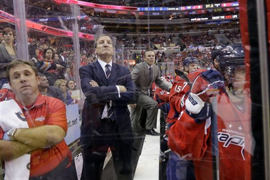 Washington Capitals coach Adam Oates, center, puts a foot on the bench to get a better view of the action, next to assistant coach Tim Hunter, second from left, in the third period of an NHL hockey game against the Toronto Maple Leafs Tuesday, Feb. 5, 2013 in Washington. The Maple Leafs won 3-2. (AP Photo/Alex Brandon)