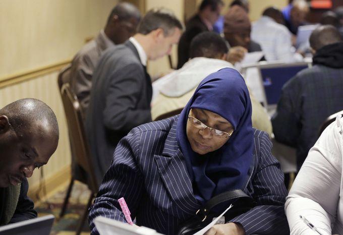 Karina Abdul-Haqq (center) of Newark, N.J., completes a job application at a job fair sponsored by Swissport in Newark on Wednesday, Feb. 6, 2013. (AP Photo/Mark Lennihan)