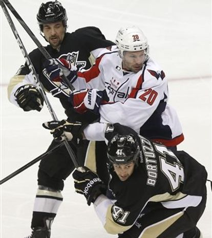 Pittsburgh Penguins' Robert Bortuzzo (41) and Deryk Engelland (5) hit Washington Capitals' Troy Brouwer (20) in the NHL hockey game between the Pittsburgh Penguins and the Washington Capitals on Thursday, Feb. 7, 2013 in Pittsburgh. (AP Photo/Keith Srakocic)