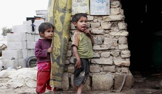 Children stand in front of their house at a compound for displaced people in Baghdad's southeastern Zaafaraniyah district, Wednesday, Feb. 6, 2013. An estimated 1.55 million people are currently displaced inside Iraq due to sectarian violence that threatened their lives. (AP Photo/ Hadi Mizban)
