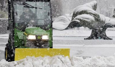 Kevin Quick plows a slushy mix in front of an M&T Bank branch in Buffalo, N.Y., during a winter storm on Feb. 8, 2013. (Associated Press)