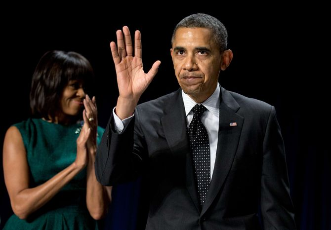 First lady Michelle Obama applauds as President Obama waves after speaking at the National Prayer Breakfast in Washington on Feb. 7, 2013. (Associated Press)