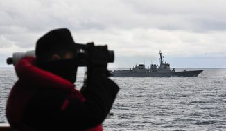 A South Korean sailor uses a binoculars as South Korean warship sails during their three-day military drills in South Korea's East Sea on Feb. 6, 2013. (Associated Press/Korea Pool via Yonhap)