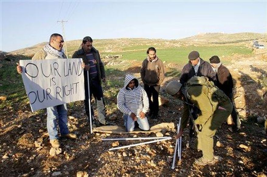 ** FILE ** Israeli soldier picks up parts of a tent previously set up by Palestinian activists in Yatta, south of the West Bank city of Hebron, Saturday, Feb. 9. Palestinian activists set up a tent village to protest the settlement building in the area. (Associated Press)