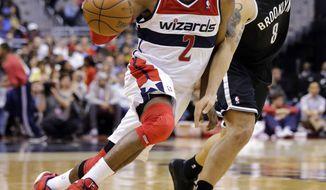 Washington Wizards guard John Wall (2) drives past Brooklyn Nets guard Deron Williams (8) during the second half of an NBA basketball game Friday, Feb. 8, 2013, in Washington. Wall had 15 points as the Wizards won 89-74. (AP Photo/Alex Brandon)
