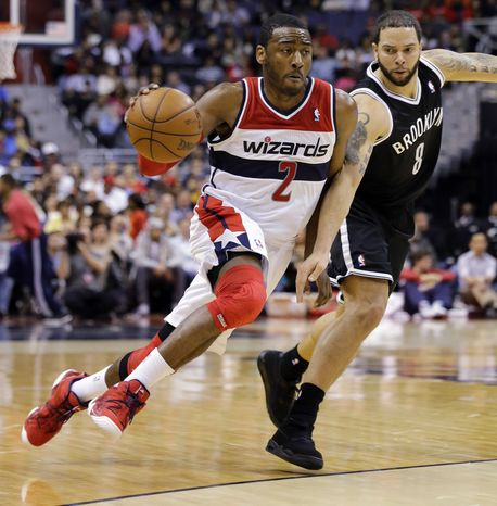 Washington Wizards guard John Wall (2) drives past Brooklyn Nets guard Deron Williams (8) during the second half of an NBA basketball game Friday, Feb. 8, 2013, in Washington. Wall had 15 points as the Wizards won 89-74. (AP Photo/Alex Brandon)