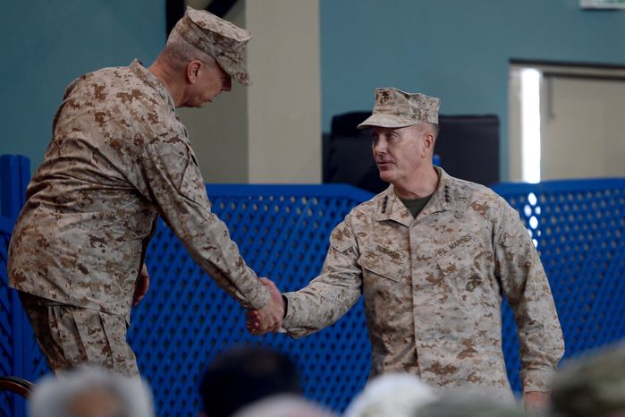 U.S. Marine Gen. Joseph F. Dunford (right) shakes hands with U.S. Marine Gen. John Allen (left), the outgoing NATO commander, during a change-of-command ceremony at the International Security Assistance Force headquarters in Kabul, Afghanistan, on Sunday, Feb. 10, 2013. Gen. Dunford takes charge at a critical time for President Obama and the military as foreign combat forces prepare to withdraw from Afghanistan by the end of 2014. (AP Photo/Massoud Hossaini, Pool)