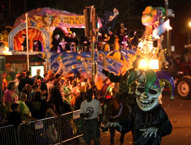 """The 460 riders of the satirical Krewe D'Etat turn onto St. Charles Avenue as they roll down the traditional Uptown route with their 22-float presentation titled """"The Dictator's Reading Room"""" on Friday, Feb. 8, 2013, in New Orleans during pre-Mardi Gras celebrations. (AP Photo/The Times-Picayune, Michael DeMocker)"""