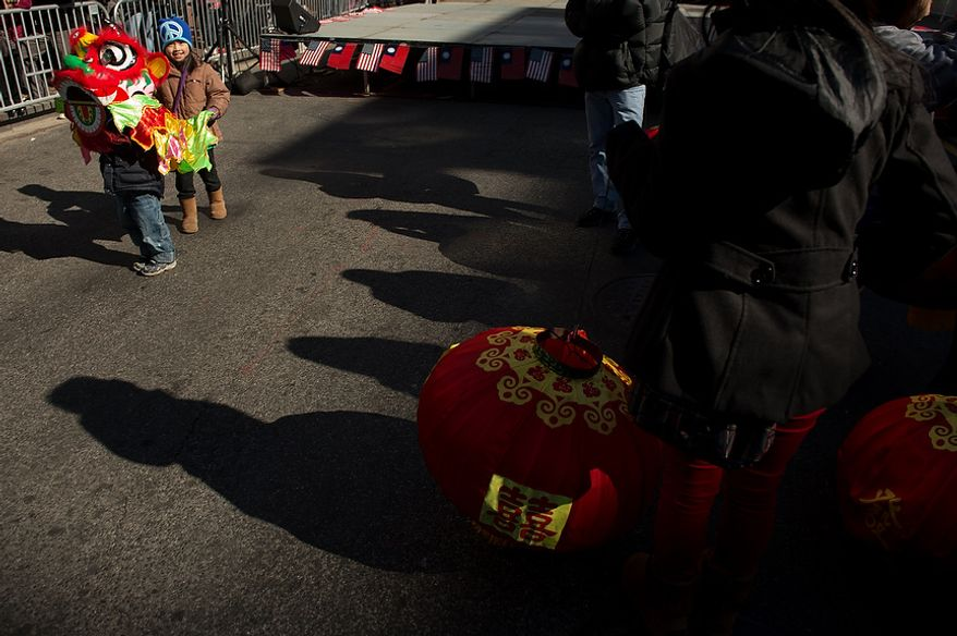 Siblings James, 4, and Olivia, 8, Yuen of Germantown, Md., left, dress as a small dragon before Washington, D.C. celebrates the Chinese New Year with a parade down H Street in Chinatown for the year of the snake, Washington, D.C., Sunday, February 10, 2013. (Andrew Harnik/The Washington Times)
