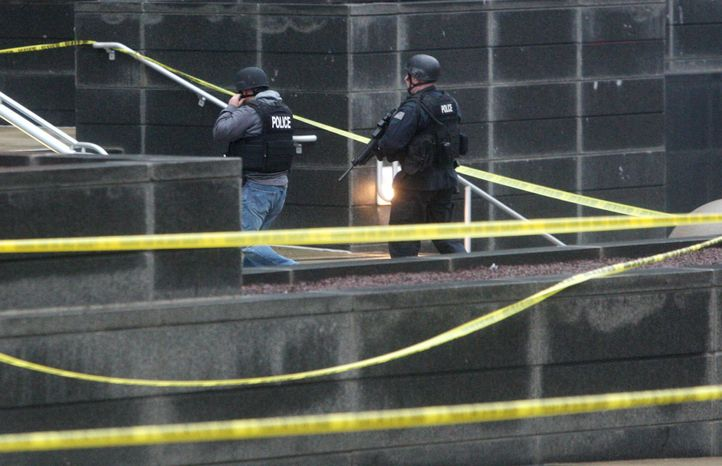 Heavily armed police enter the New Castle County Courthouse, Monday morning, Feb. 11, 2013, in Wilmington, Del. The mayor of Wilmington, Del., says a man suspected of killing his wife and wounding two others at the New Castle County Courthouse has been killed by police. (AP Photo/The News Journal/William Bretzger)