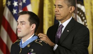 President Obama bestows the Medal of Honor on retired Staff Sgt. Clinton Romesha on Monday, Feb. 11, 2013, in the East Room of the White House in Washington. (AP Photo/Pablo Martinez Monsivais)