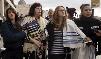 Wrapped in Jewish prayer shawls, Rabbi Susan Silverman, second left, the sister of comedian Sarah Silverman, not seen, along with her teenage daughter Hallel Abramowitz, second right, are detained by police officers in Jerusalem's Old City, Monday, Feb. 11, 2013. (AP Photo/Tali Mayer)